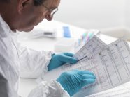 Forensic scientist examining DNA sequencing results. — Stock Photo
