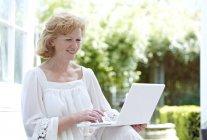 Mature woman using laptop in garden. — Stock Photo
