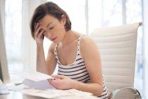 Mujer estresada mirando hacia abajo las facturas . - foto de stock