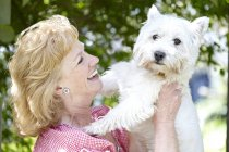 Mature woman holding pet dog. — Stock Photo