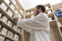 Farmacêutico selecionando medicamentos em caixas nas prateleiras da farmácia . — Fotografia de Stock
