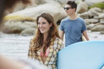 Woman on beach with surfboard and man in background. — Stock Photo