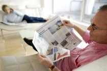 Man reading newspaper while relaxing at home — Stock Photo
