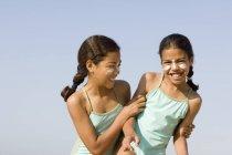 Сестры с солнцезащитным кремом на лицах играют в бои на пляже . — стоковое фото