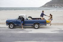 Woman getting on pick up truck with friends on beach. — Stock Photo