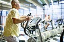 Старший чоловік, використовуючи вправу машини в тренажерний зал. — стокове фото