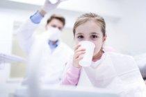 Retrato de menina água potável na clínica odontológica . — Fotografia de Stock
