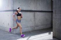 Woman wearing headphones running — Stock Photo