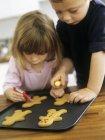Vorschulkind Geschwister frisch gebackene Kekse mit Zuckerguss verzieren — Stockfoto