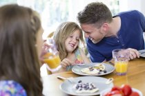 Pai e filhas sorrindo enquanto toma café da manhã à mesa . — Fotografia de Stock