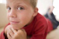 Ritratto di ragazzo sorridente sdraiato sul pavimento . — Foto stock
