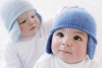 Bébés garçons en chapeaux tricotés jouant sur fond blanc. — Photo de stock