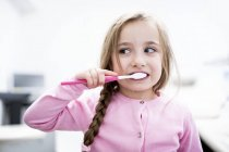 Portrait of little girl brushing teeth. — Stock Photo