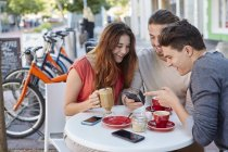 Friends sitting in cafe and using smartphone. — Stock Photo