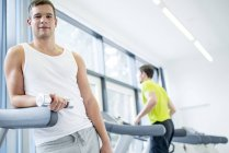 Man holding dumbbell and leaning on treadmill in gym. — Stock Photo