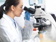 Científica viendo muestras de tejido bajo microscopio . - foto de stock