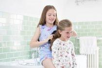 Girl brushing sister hair in bathroom. — Stock Photo