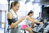 Woman using smartphone while exercising in gym. — Stock Photo