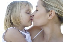 Mutter und Tochter küssen im freien. — Stockfoto