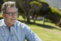 Senior homme portant des lunettes et chemise, assis sur la Prairie et souriant — Photo de stock