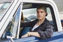 Mann blickt durch geöffnetes Autofenster in Kamera. — Stockfoto