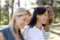 Трьох молодих подруг ходьба і посміхаючись в парку. — стокове фото