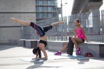 Frau in Yogaposition mit Freund beobachten — Stockfoto