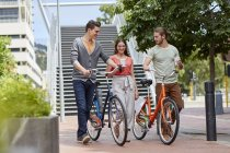 Friends walking with bikes and coffee on street. — Stock Photo