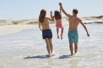 Mother and father lifting daughter on beach. — Stock Photo