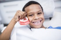 Portrait of boy holding dentures and smiling. — Stock Photo