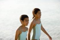 Систеры в купальниках прогуливаются по пляжу в стороне . — стоковое фото