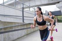 Young women running in urban scene. — Stock Photo