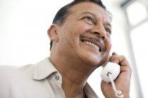 Porträt eines lächelnden reifen Mannes, der am Schnurtelefon spricht. — Stockfoto