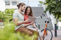 Couple sitting on street wall with digital tablet. — Stock Photo