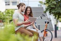 Пара сидящих на стене с цифровым планшетом . — стоковое фото