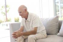 Ältere Mann sitzt allein auf sofa — Stockfoto
