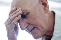 Retrato del hombre mayor con la mano en la frente . - foto de stock