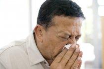 Hombre maduro estornudando en el pañuelo . - foto de stock