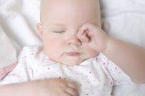 Säugling Baby reiben Augen im Bett. — Stockfoto