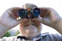 Menino obeso usando binóculos ao ar livre . — Fotografia de Stock