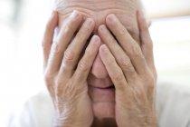 Retrato del hombre mayor cubriendo la cara con las manos . - foto de stock