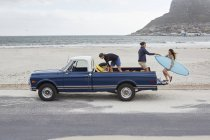 Woman getting with men on pick up truck on beach. — Stock Photo
