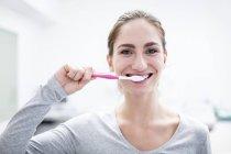 Молодая женщина чистит зубы, портрет . — стоковое фото