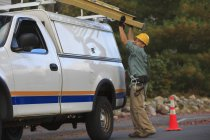 Lineman putting ladder on truck at working site. — Stock Photo