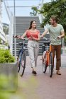 Young couple walking with bikes on street. — Stock Photo