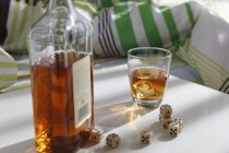 Whiskey bottle with dice on table. — Stock Photo