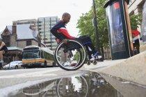 Человек в инвалидной коляске переезжает бордюр — стоковое фото