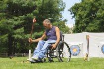 Mann mit Querschnittslähmung im Rollstuhl bereitet sich auf Bogenschießen vor. — Stockfoto