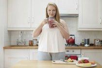 Mujer bebiendo batido en la cocina - foto de stock