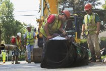 Construction workers cutting water main with gas powered saw. — Stock Photo